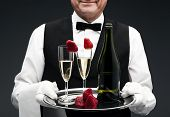 picture of flute  - butler with two champagne flutes and strawberries on tray - JPG