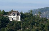 stock photo of acadian  - a seaside mansion peaking out of the acadian forest - JPG
