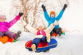 picture of snow-slide  - Children with arms high sliding down on the tubes during frost winter day together - JPG