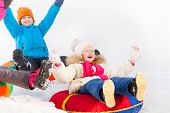 image of snow-slide  - Laughing girl and boy sliding down on the tubes during frost winter day together - JPG