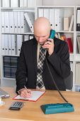 picture of bald head  - young businessman with bald head in the office is calling - JPG