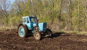 pic of plowed field  - Blue tractor plowing a field in spring - JPG