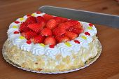 image of hand cut  - Hand is cutting cream cake with fresh strawberries on the plate on the wooden table - JPG