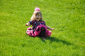 Happy little girl sitting on the green lawn