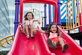 stock photo of playground  - Two happy girls sliding together at the playground - JPG