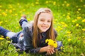 image of little girls photo-models  - spring portrait of smiling girl lying in meadow holding bouquet of dandelions - JPG