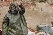 picture of gas mask  - Man with gas mask and green military clothes explores dead bird after chemical disaster - JPG