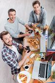 pic of indoor games  - Top view of three young men playing computer games and eating pizza while sitting at the desk - JPG