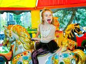foto of carnival ride  - cute little girl riding on a carousel - JPG