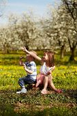 image of orchard  - Girl sitting with boy in a blooming orchard - JPG