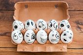 stock photo of egg-laying  - Top view of funny eggs with different emotions laying in container on the wooden desk - JPG