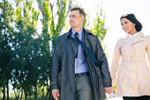 stock photo of walking away  - Happy beautiful couple walking outdoors and looking away - JPG