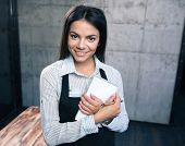 picture of apron  - Smiling pretty female waiter in apron with notepad and pen in cafe - JPG