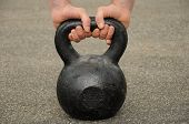 stock photo of kettlebell  - Man is holding on to a 32 kilo kettlebell - JPG