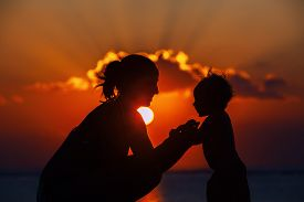 picture of sea life  - Silhouette of happy beautiful mother smiling to joyful baby boy on sea beach on background of sunset sky with clouds - JPG