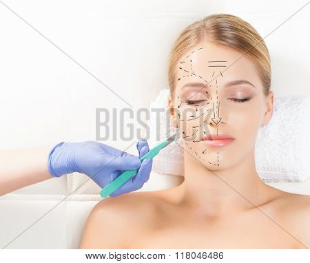 Beautiful woman getting face lifting operation. Drawing arrows and a scalpel over her face. Aging an