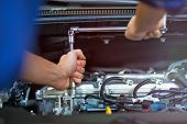 Mechanic working on engine in auto repair shop  poster