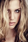 closeup portrait of young beautiful blonde woman with long curly hair and natural fresh make-up and