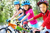 Three little children riding their bikes