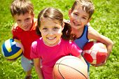 stock photo of volleyball  - Portrait of three little children with balls looking at camera and smiling - JPG