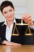 Woman holding the justice scale in her office