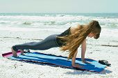 Woman Doing Yoga Exercise On Beach In High Plank Pose