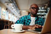 Busy young man with laptop typing while sitting in cafe during coffee-break poster