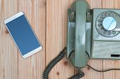 Retro Rotary Telephone Or Vintage Phone With Cable And New Cell Phone Or Smart Phone On Wood Table, poster