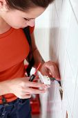 handywoman setting an outlet in a wall