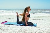 Woman Doing Yoga Exercise On Beach In Kapotasana Or Pigeon Pose