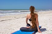Woman Doing Yoga Exercise On Beach In Rotated Half Lotus Pose Or Ardha Padmasana