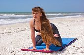 Woman Doing Yoga Exercise On Beach Kneeling Lotus Pose