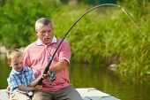 stock photo of spinner  - Photo of grandfather and grandson pulling rod together while fishing - JPG