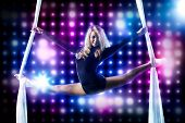 Young woman gymnast. On black background with lights.