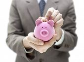 stock photo of coin slot  - Businessman putting coin into the piggy bank - JPG