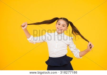 poster of Long And Healthy. Cute Small Schoolgirl Holding Long Hair Ponytails On Yellow Background. Adorable L