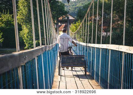 poster of Man Traveler Crossing Bridge. Travel Photography Of Man Crossing Bridge. Traveling Man With Bicycle