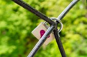 The Lock, A Symbol Of Love And Loyalty, Hangs On Iron Bars. Red Heart Painted On The Lock. A Piece O poster