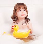 cute one year old girl taking a bath with foam and playing with a toy duck