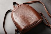 Brown Backpack Made Of Textured Brown Leather On A Black Stone Background. Elegant Golden Brown Wome poster