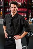 Portrait of handsome barman standing in front of the bar