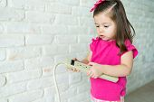 Adorable Small Girl Looking At Extension Cord By Wall In Living Room At Home poster