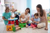 Adorable Toddlers Playing With Colorful Toys And Mothers In Nursery Room. Nursery Babies Playing Wit poster
