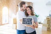 Middle age senior couple moving to a new house, smiling happy in love with apartmant holding a black poster