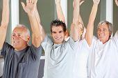 Happy senior people doing gymnastics exercises in gym
