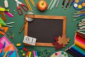 Blank blackboard, autumn leaves, stationery accessories on green background. Top view, copy space. S poster