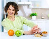 Постер, плакат: Диета Диеты концепции Здоровая пища Красивая молодая женщина выбор между фрукты и сладости