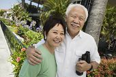stock photo of early 60s  - Smiling Couple with Binoculars - JPG