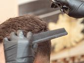 Close Up On Males Hair In Barbershop. Hairstylists Hands In Black Rubber Gloves. Master Cutting Hair poster