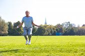 Determined senior man working out with skipping rope in park poster